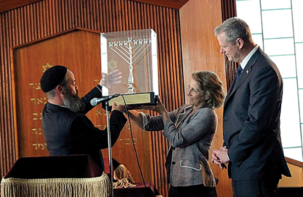 Massachusetts Gov. Charlie Baker and his wife Lauren received a gift of a menorah from Rabbi Yossi Lipsker at the twenty-third anniversary celebration at Chabad of the North Shore in 2015.