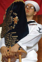 Jesse Kopelman, USS Harry S. Truman's Jewish Lay Leader, holds a holy Jewish Torah, one of the few scrolls from Lithuania to survive the Holocaust, which was presented to Truman.