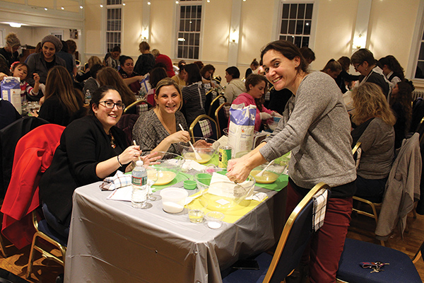 Standing to the right is Rebbeca Spiewak, seated to the left is Debbie Golub Sass, and center is Jamie Tov, at the North Shore Challah Bake.