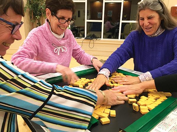 Rachelle Rosenbaum, Carla Greenberg, and Amy Saltz shuffle tiles. Photos by Michael Wittner/Journal Staff