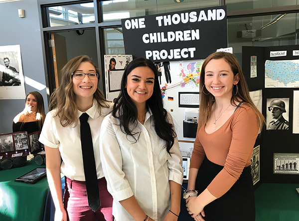 "Essex North Shore seniors Luisa Buendia, Jazlynn Martinez, and Jessica Santiago pose in front of their ""1,000 Children Project"" exhibition. The students profiled how children were rescued and relocated from Europe during the Holocaust."