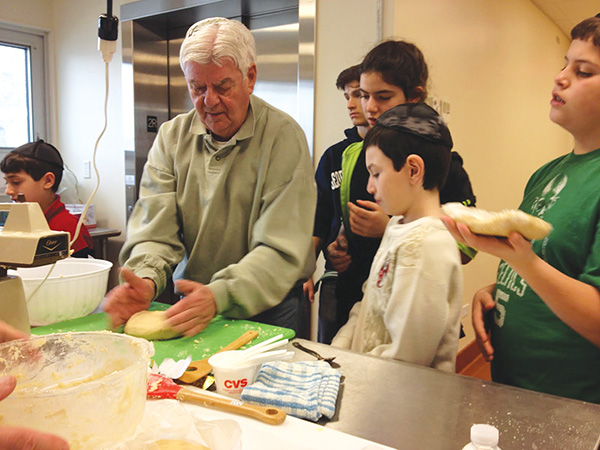 Hebrew school students learn to make challah at an intergenerational event.