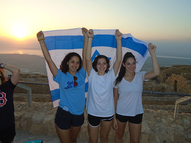 Jenna Tabenkin, Adriana Kotler, and Arielle Cushinsky raise the Israeli flag at Masada.