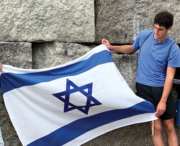 Adam Zamansky, of Marblehead, holds the Israeli flag at Treblinka.