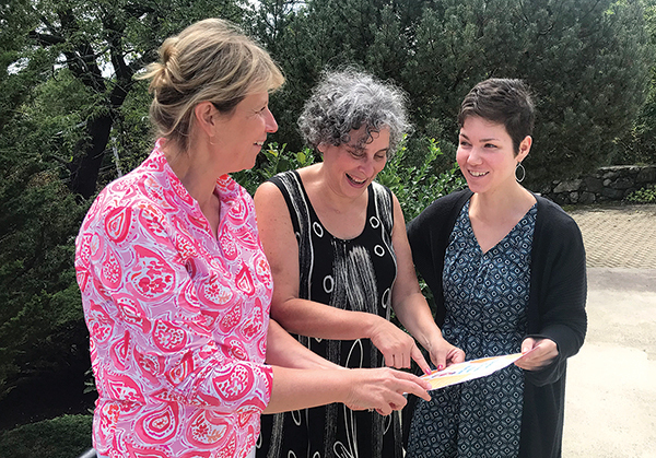 Evelyn Rothbard, a volunteer at Temple Sinai who coordinates its participation in the Honey From The Heart program, looks over this year's program flyer with temple executive director Susan Weiner and temple administrative assistant Meg Gatterman. Photo: Rich Tenorio