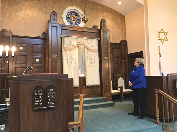Former Temple President Debby Cherry stands on the bimah at Temple B'nai Israel.