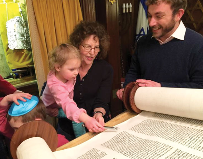 Susan Silbovitz and her granddaughter Cara Miller read from the Torah at a Tot Shabbat at Temple Emanuel in Wakefield, alongside Rabbi Greg Hersh.