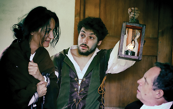 Accused witch Sarah Good (Verjana Abazaj) explains her innocence to Judge Saltonstall (Ben Evett) as the jailer (Noah Greenstein) stands guard.