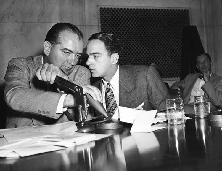 Mandatory Credit: Photo by AP/REX/Shutterstock (6648726a) Senator Joseph McCarthy covers the microphones with his hands while having a whispered discussion with his chief counsel Roy Cohn during a committee hearing, in Washington. The entire event of the Senate subcommittee hearings on the Army-McCarthy charges is broadcasted live on television and radio SENATOR MCCARTHY, WASHINGTON, USA
