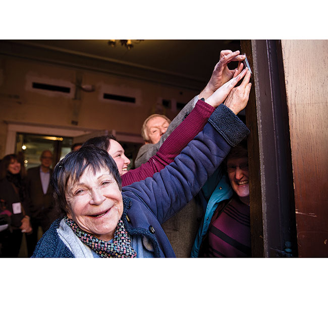 Diana Shulman helps hang a mezuzah to the front doorpost with three of her family members that span three generations. Shulman and her family are descendants of two different founding families of the Vilna Shul. / Photo: Leah LaRiccia Photography