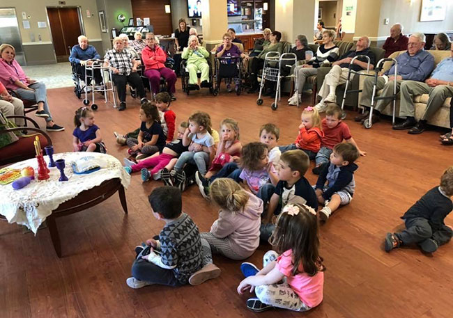 """Each week,preschoolers and their""""grandfriends"""" celebrate Shabbat together in the common room of Kaplan Estates."""