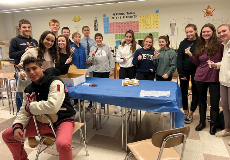 The newly-formed Jewish Student Union at Marblehead High School enjoys sufganiyot for Hanukkah.