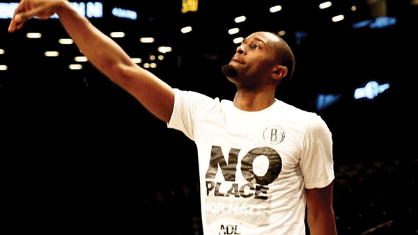 """Brooklyn Nets forward Theo Pinson  at the Barclays Center in Brooklyn wearing a """"No Place for Hate"""" T-shirt. Photo: Brooklyn Nets/Twitter"""