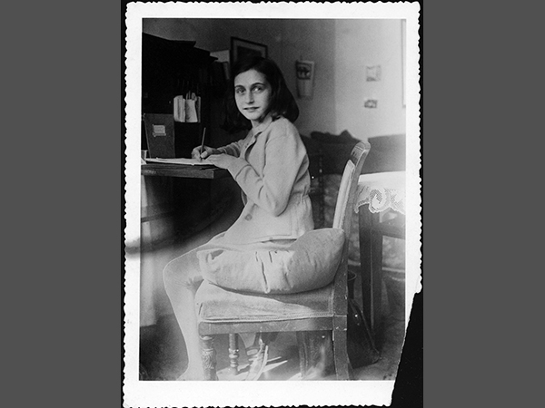 Anne Frank writing at her desk at home in 1941.