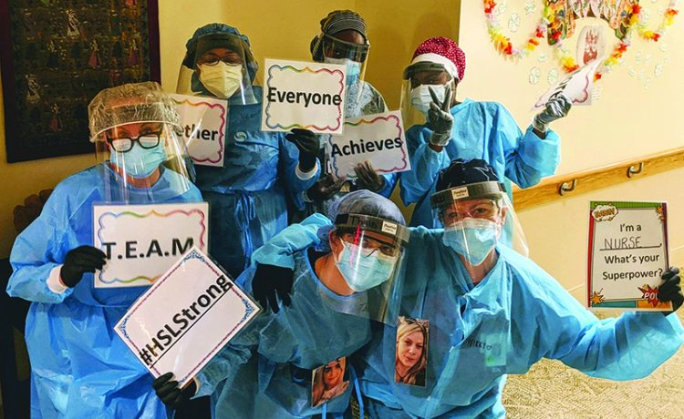 """Nicole DeMayo, lower right, holds a sign that reads, """"I'm a nurse."""" Courtesy Hebrew SeniorLife"""