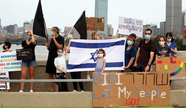 Like their counterparts in Israel, dozens of Greater Boston Israelis are holding weekly protests. They are demanding that Prime Minister Benjamin Netanyahu resign. Photo: Tess Scheflan, Activestills
