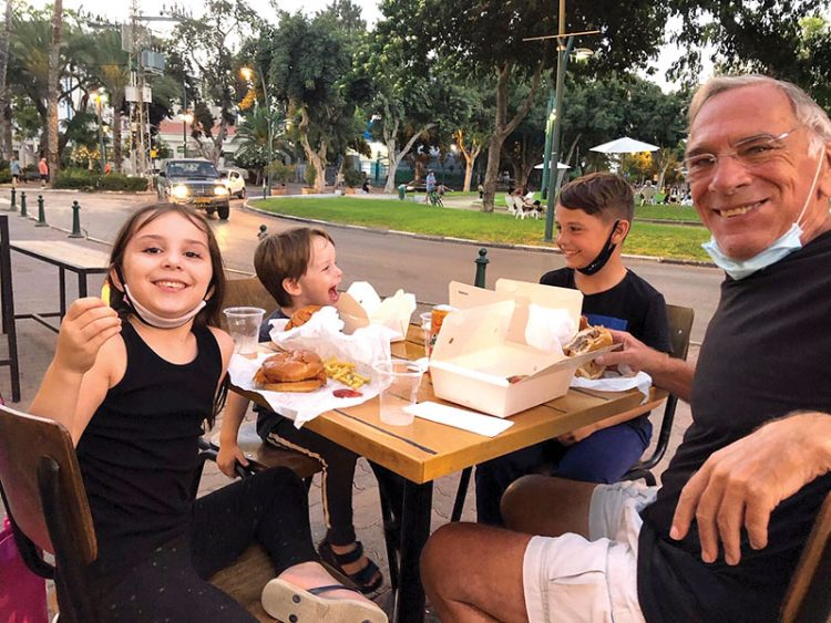 Joseph Greenberg, right, has burgers with his grandchildren in Israel, left to right, Maya, 7, Yuval, 4 and Aviv, 9. A trip to visit his family in Israel resulted in Greenberg becoming stuck in the country due to the pandemic. The former Brookline resident decided to remain in Israel and make Aliyah.
