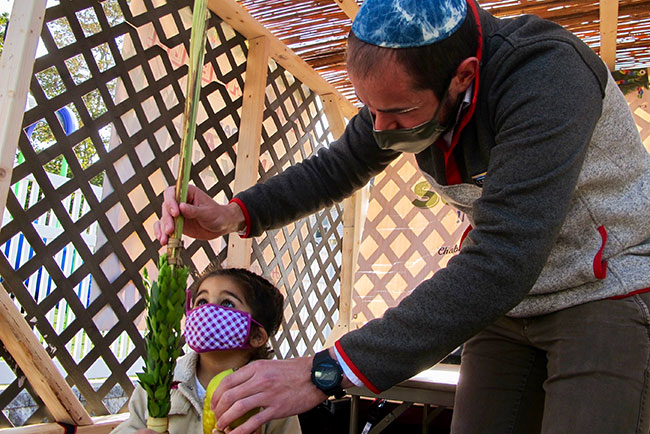 Rabbi Sruli Baron instructs Helena Wyner, 2, of Aleph Academy,  how to hold the lulav and etrog in the Sukkah Mobile.
