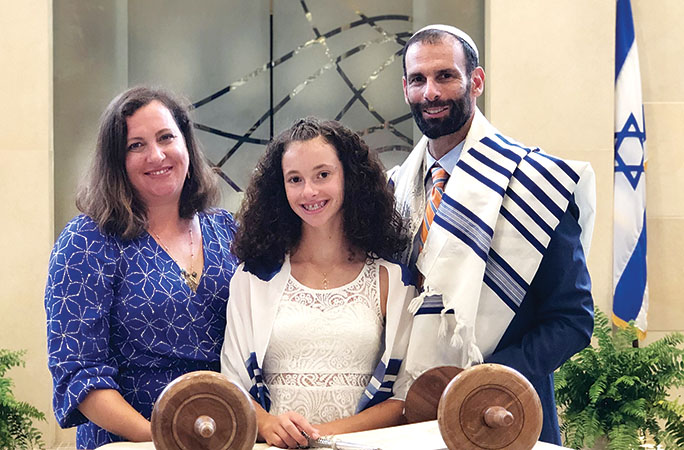 Liora Ragozin with her mother, Sarah Plymate (left) and her father, Congregation Shirat Hayam Rabbi Michael Ragozin (right) smile amid the celebration of Liora's bat mitzvah and her reading from the Torah.