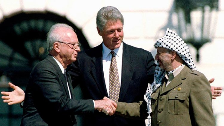 Israeli Prime Minister Yitzhak Rabin, U.S. President Bill Clinton, and Yasser Arafat at the Oslo Accords signing ceremony in 1993.