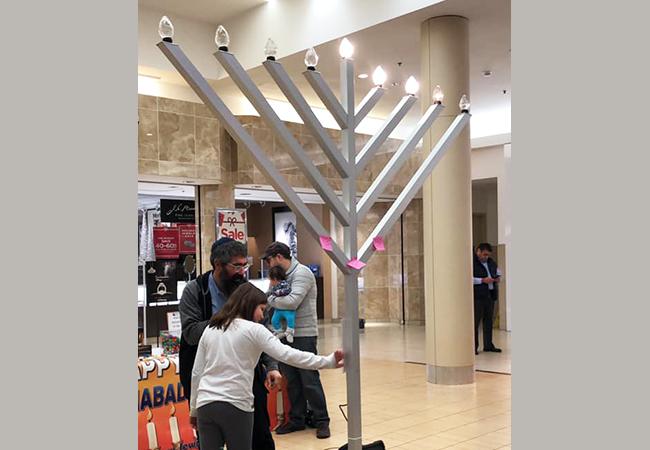 Rabbi Nechemia Schusterman lights the menorah at the Northshore Mall in Peabody. Courtesy photo: Chabad of Peabody