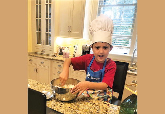 Benjamin Pourati of Newbury­port is shown participating in PJ Library Kids Cooking at Home, a virtual Lappin Foundation program held before Rosh Hashanah.
