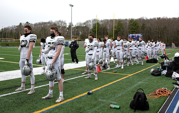 The Duxbury High football team stands for the national anthem before last week's game. Photo: Karen Wong