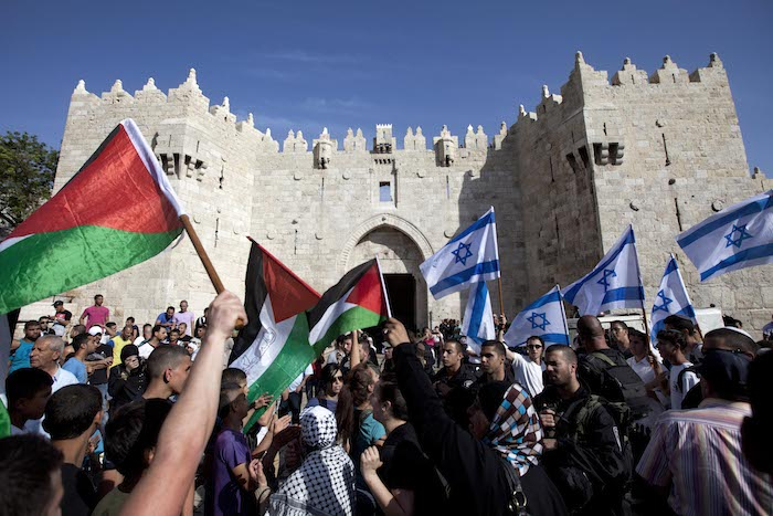 Israelis and Palestinians wave flags as Israelis march celebrating Jerusalem Day outside Damascus Gate in Jerusalem's old city in 2013.