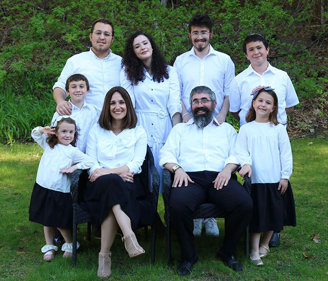Rabbi Nechemia Schusterman (front, middle right), Raizel Schusterman (front, middle left), Henny, (far left), Sarah (far right); Top row: Levi, Mordy, Rochel Leah, Mendy, and Shaya.