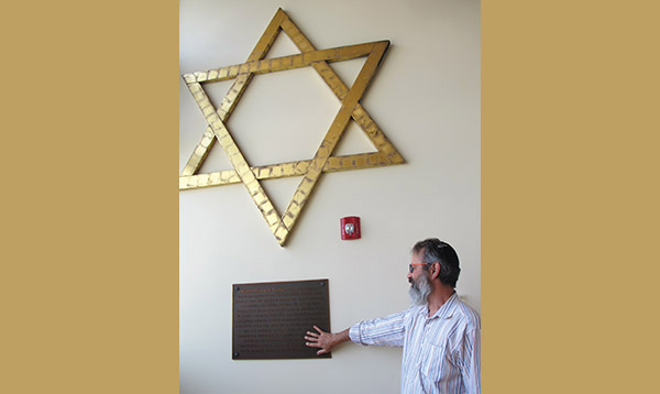 Rabbi Steven Lewis of Temple Ahavat Achim touches a plaque dedicated to the congregation's former longtime rabbi, Myron S. Geller. It had been salvaged from the temple's former building that burned down in December 2007. Photo: Ethan M. Forman/Journal Staff